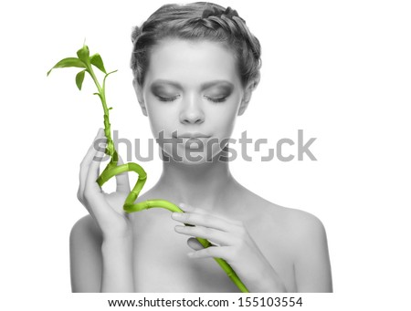 Close-up portrait of beautiful young woman with green bamboo. Isolated white background, monochrome. - stock photo
