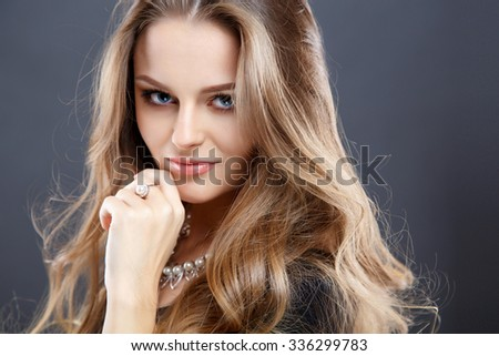 Close-up portrait of beautiful young woman with luxury jewelry and perfect make up. Fashion beauty portrait