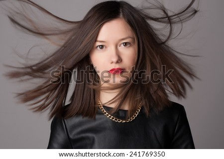 Close-up portrait of beautiful young woman with medium short hair. Fashion shot. Healthy hair concept. Studio portrait and jewelry. - stock photo