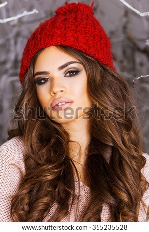 Close up portrait of  beauty  winter girl in frosty winter park .Beautiful young woman in red knitted hat, wavy  amazing hairstyle , full lips and  bright make up. - stock photo