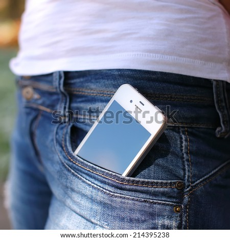 close-up portrait of Black smartphone in back pocket of girl's jeans - stock photo