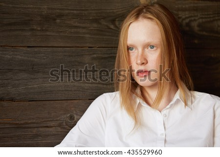 Close up portrait of Blond Caucasian woman with blue eyes on wooden background. Young female looking pensively in front of her with slightly careless hair and thoughtful eyes. Stylish photo. - stock photo
