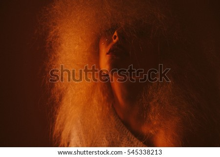 close-up portrait of blonde Afro curls low key