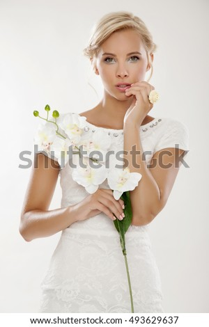 Close up portrait of blonde young bride in white wedding dress happy smiling with flowers in hands isolated on white background