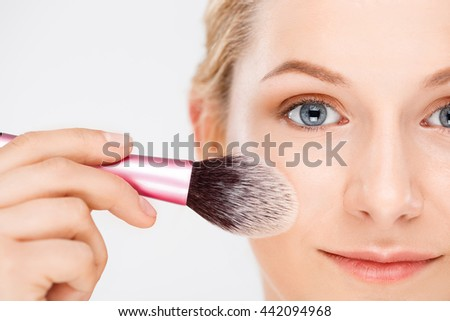 Close up portrait of blonde young pretty girl doing make-up with brush, smiling, looking at camera, over white background.