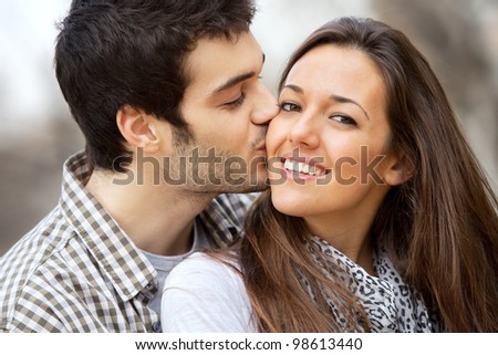 Close up portrait of boy kissing girlfriend on cheek outdoors. - stock photo