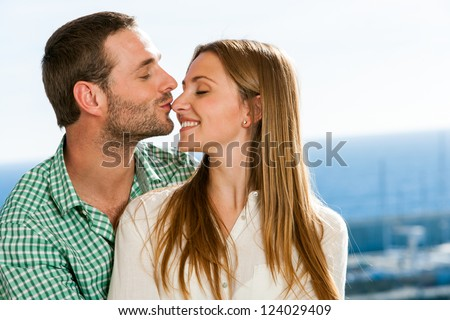 Close up portrait of boyfriend kissing girl on nose outdoors.