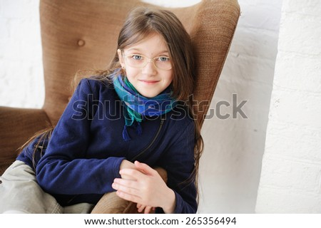 Close-up portrait of brunette child gir in scarf and blue jacketl in glasses - stock photo
