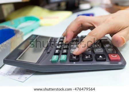 Close up portrait of business woman hand while using press calculator