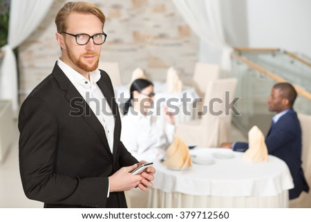 Close-up portrait of businessman holding mobile phone in restaurant. Handsome man in business suit and glasses looking at camera. - stock photo