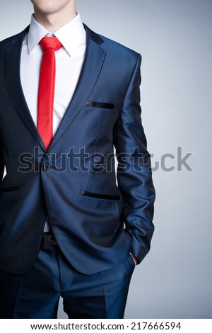 Close up portrait of businessman in suit with red tie standing with his hands in pockets - stock photo