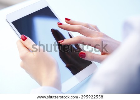 Close-up portrait of businesswoman holding hands digital tablet and touching the screen. Young professional working with tablet.  - stock photo