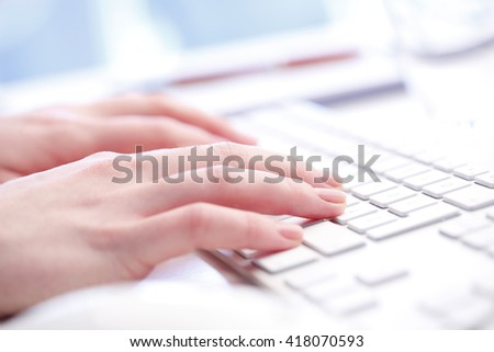 Close-up portrait of businesswoman's hand typing on laptop keyboard.