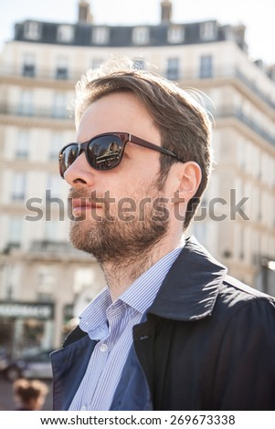 Close up portrait of caucasian adult man in sunglasses - fashion accessories. Paris buildings as background.  - stock photo