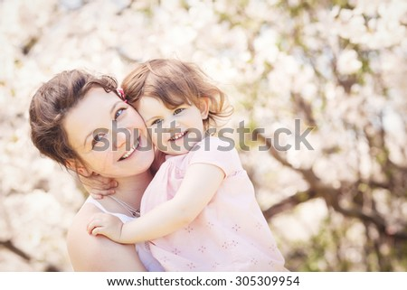 Close up portrait of caucasian mother in white dress holding hugging her daughter in pink clothes smiling on sunny spring summer day in park outside