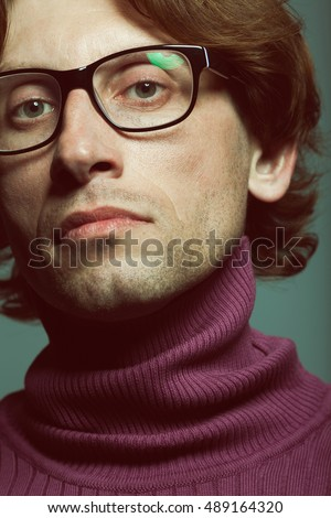 Close up portrait of charismatic young man wearing trendy stylish eyeglasses and violet polo neck. Guy is looking like famous french fashion designer of 60s-70s. Retro style. Studio shot
