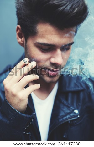 Close up portrait of charming fashionable man exhaling cigarette smoke while looking down, trendy attractive man blowing smoke out of his mouth standing on grey background, filtered image, blue flare - stock photo