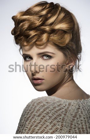 close-up portrait of charming young girl with elegant creative hair-style and natural make-up, looking in camera  - stock photo