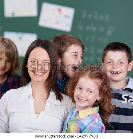 Close up portrait of cheerful students with teacher at the classroom