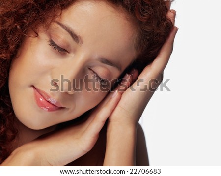 Close-up portrait of cheerful young adult girl with closed eyes