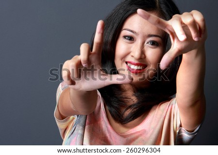 Close up portrait of cheerful young beauty woman making frame with her finger