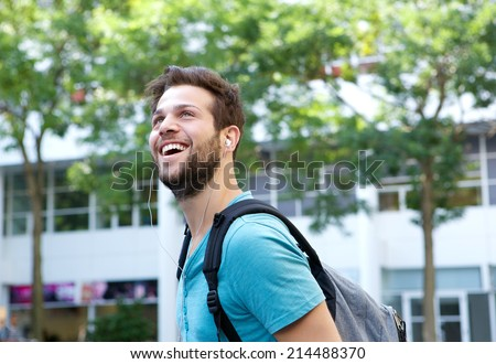 Close up portrait of  cheerful young man smiling with bag outdoors - stock photo