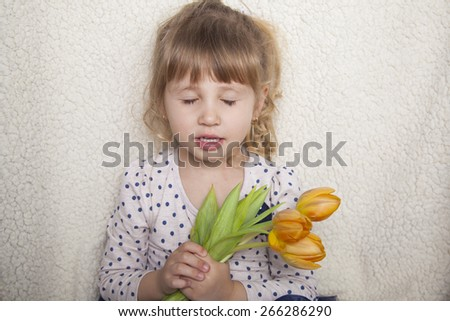 Close-up portrait of child girl. Close up photo of cute girl isolated on white background and holding nice bouquet of yellow tulips - stock photo
