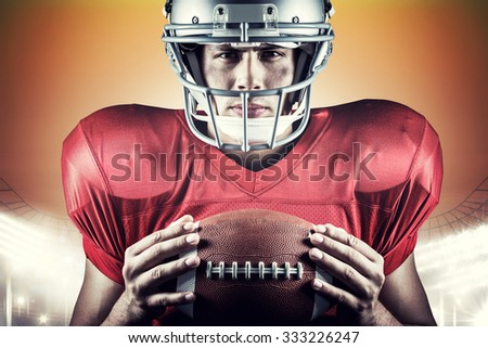Close-up portrait of confident American football player holding ball against rugby stadium