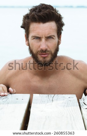 Close up Portrait of Confident Athletic Handsome Man with No Shirt Posing at the Sea