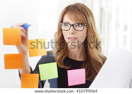 Close-up portrait of confident businesswoman working at idea board and using sticky notes at transparent wall.