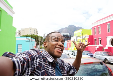 Close up portrait of cool young african guy taking a selfie while out on the city street - stock photo