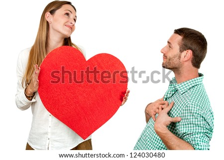 Close up portrait of couple playing around with big red heart symbol.Isolated on white background. - stock photo