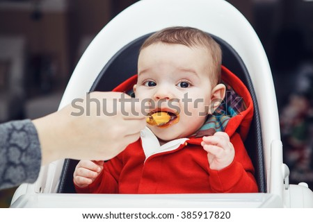 Close-up portrait of cute adorable Caucasian little baby boy with dark black eyes sitting in high chair in kitchen looking in camera eating meal puree, mother feeds her son - stock photo