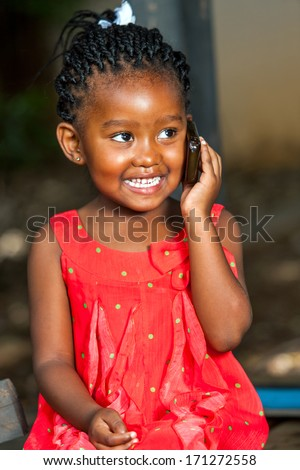 Close up portrait of cute african girl having conversation on smart phone outdoors. - stock photo
