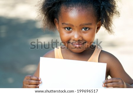 Close up portrait of cute African girl holding blank white card outdoors.