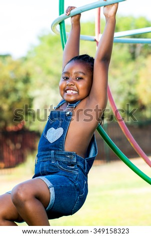 Close up portrait of cute African girl playing in park.