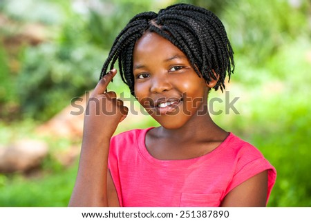 Close up portrait of Cute African girl showing braided hair outdoors in park. - stock photo