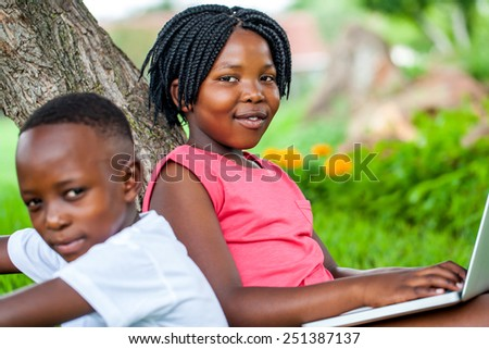 Close up portrait of cute African girl typing on laptop next to brother under tree in park.