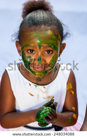 Close up portrait of cute African girl with painted face at painting session.Isolated against light background. - stock photo