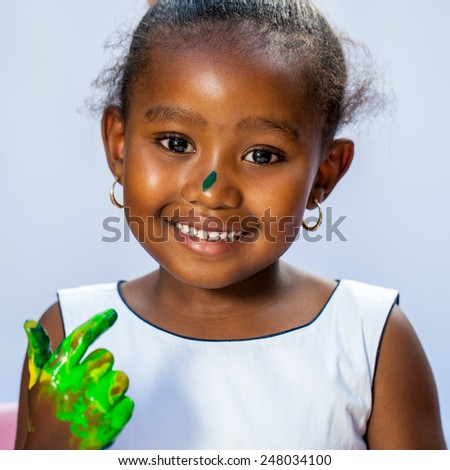 Close up portrait of cute African girl with painted hand.Isolated against light background.