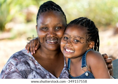 Close up portrait of Cute african mother and child embracing outdoors.