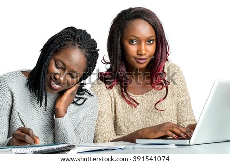 Close up portrait of cute african teen students doing homework together.Girl with braided hair writing with pen on notebook and girl with reddish hair typing on laptop.Isolated on white background. - stock photo