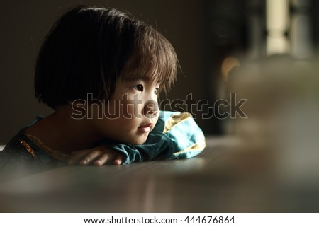 Close up portrait of cute asian girl, face of smiling, low lighting from window and selective focus. - stock photo