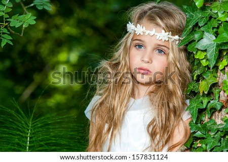 Close up portrait of cute blond girl in the woods. - stock photo