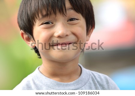 close up portrait of cute boy smiling in the park - stock photo