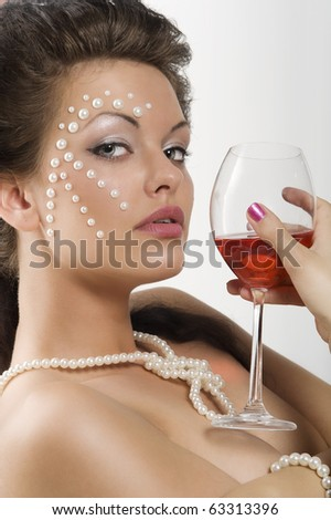 close up portrait of cute brunette with a glass of red wine and pearl on her face looking in camera