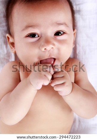 close up portrait of cute expressions of baby licking his hands
