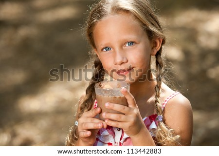 Close up portrait of cute girl drinking milk chocolate outdoors.