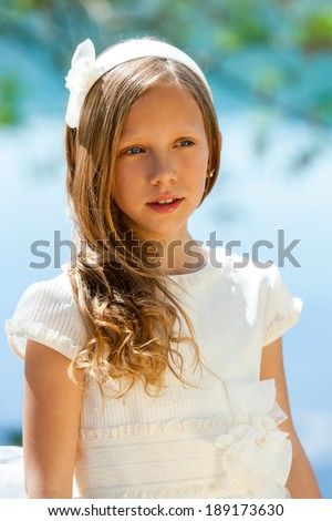 Close up portrait of cute girl in white dress and head band outdoors.