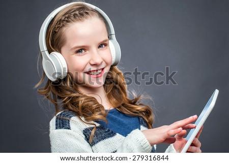 Close up portrait of cute girl wearing headphones listening music on digital tablet. - stock photo